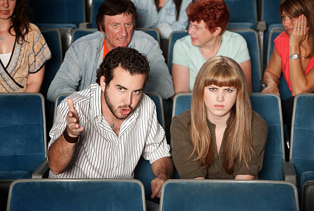 Serious Moviegoers Serious movie fans angry in a theater critic stock pictures, royalty-free photos & images