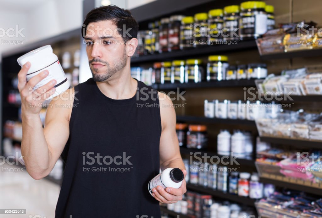 Serious muscular guy holding sport nutrition products stock photo