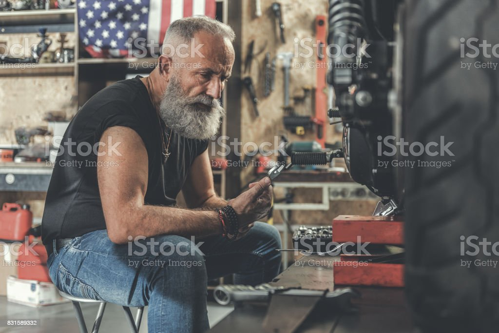 Serious old man in workshop stock photo