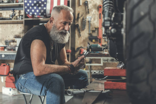 serious old man in workshop - biker stock photos and pictures