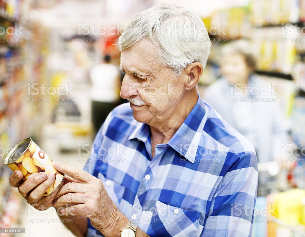Serious old man studies food label in supermarket stock photo