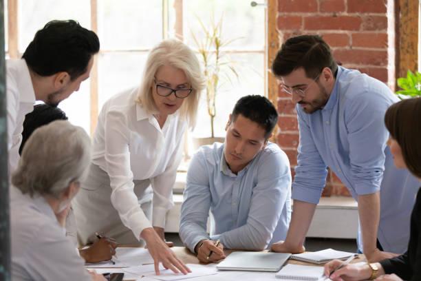 serieuze oude vrouw leadercoach leren jonge arbeiders uitleggen papierwerk - medewerkerbetrokkenheid stockfoto's en -beelden