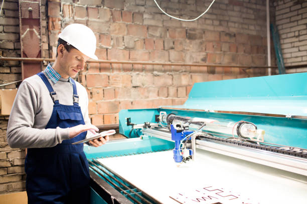 serious operator standing by cnc machine - switchboard operator stock photos and pictures