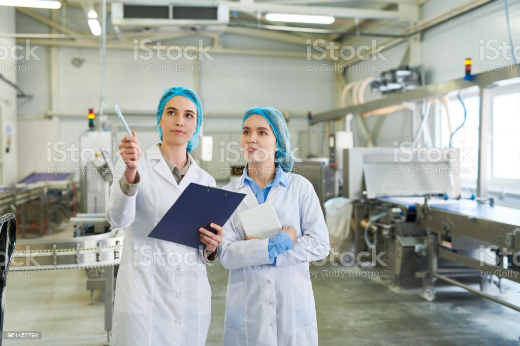 Serious pensive female food production engineer pointing with pen at machine while discussing manufacture with colleague in bakery workshop stock photo