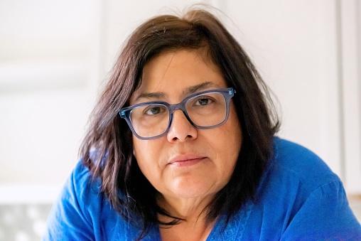 Serious pensive mature hispanic senior mature housewife looking at the camera using eyeglasses