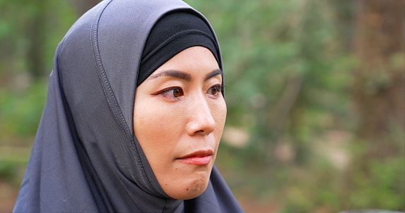 Serious pensive mid adult asian muslim woman looking away portrait wearing a hijab posing at a at a park.