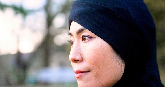 Serious pensive mid adult asian muslim woman looking away portrait wearing a turban hijab posing at a at a park.
