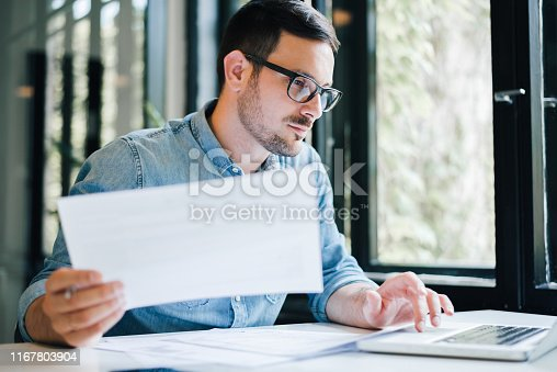 istock Serious pensive thoughtful focused young casual business accountant bookkeeper in office looking at and working with laptop and income tax return papers and documents 1167803904