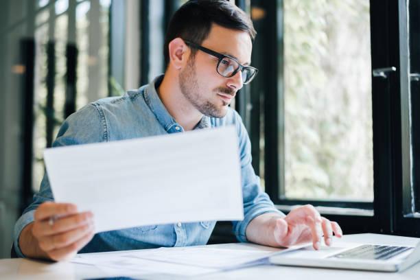 serius termenung bijaksana berfokus muda kasual akuntan akuntan pembukuan di kantor melihat dan bekerja dengan laptop dan pajak penghasilan kertas pengembalian dan dokumen - cpa vs tax advisor potret stok, foto, & gambar bebas royalti