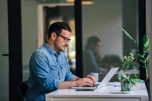 Serious pensive thoughtful focused young casual businessman or entrepreneur in office looking at and working with laptop making and typing serious important business email stock photo