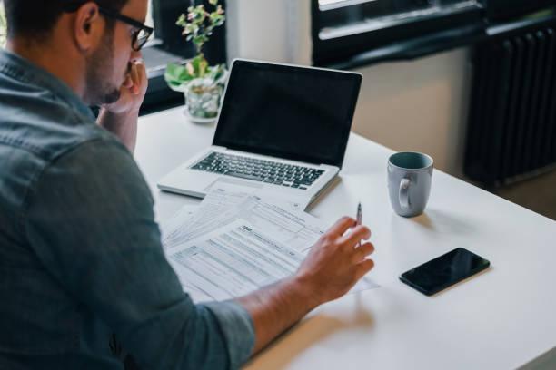 認真沉思專注的年輕休閒商人或企業家在辦公室填寫所得稅申報檔為國稅局 - small business 個照片及圖片檔