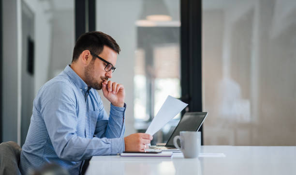 serious pensive thoughtful young businessman or entrepreneur in modern contemporary office looking at and working with laptop and paper documents making serious and important business decision - {{asset.href}} foto e immagini stock