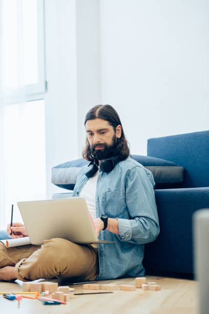 Serious person at home working with laptop and writing stock photo