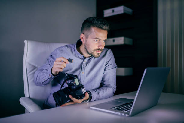 serious photographer looking at laptop and putting memory card in camera while sitting late at night in studio. - memory card stock photos and pictures