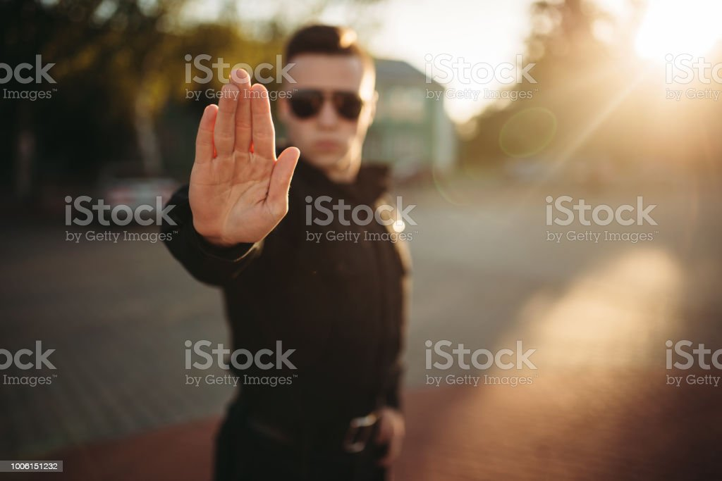 Serious police officer shows a hand stop sign stock photo