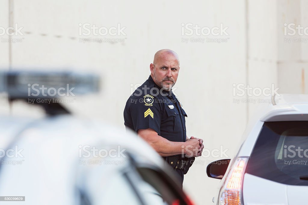 Serious police officer standing next to car stock photo