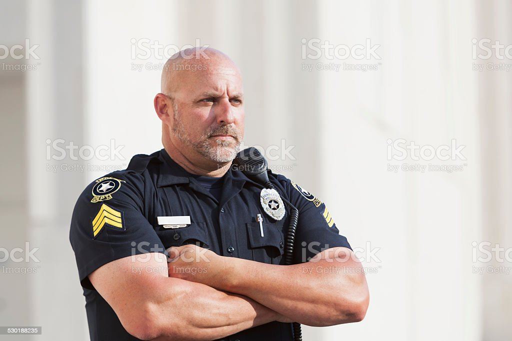 Serious police officer standing with arms crossed stock photo