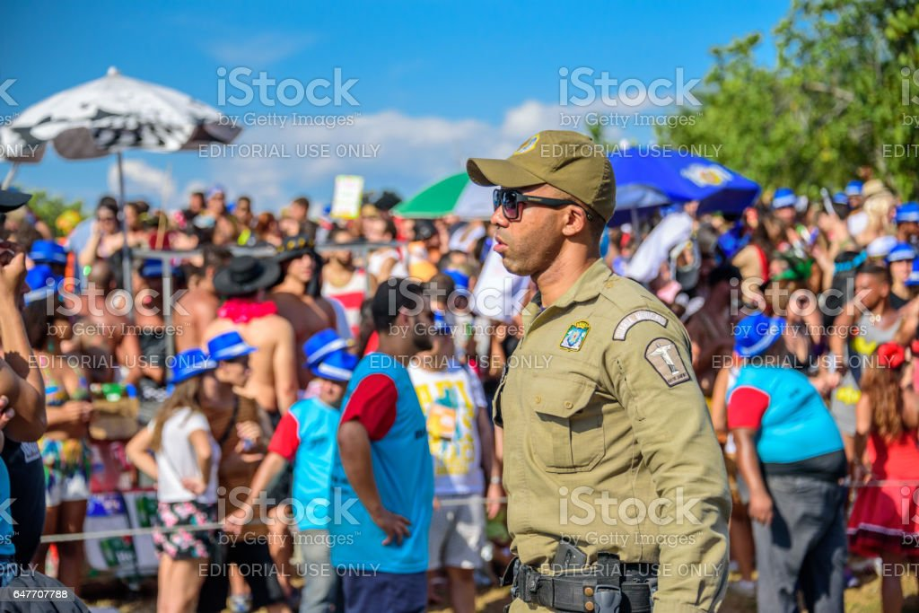 Serious policeman of Municipal Guard in sunglasses working during Bloco Orquestra Voadora, Carnaval 2017 stock photo