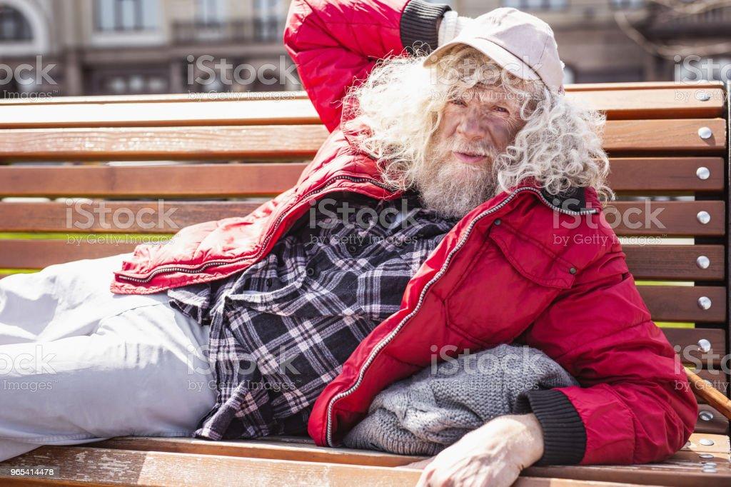 Serious poor man lying on the bench zbiór zdjęć royalty-free