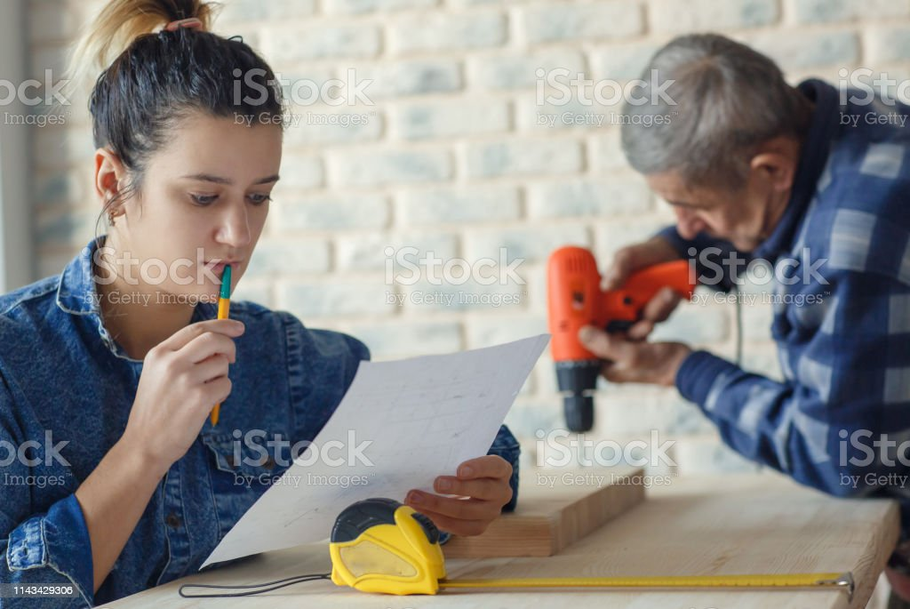 Young female designer or engineer working on apartment renovation...