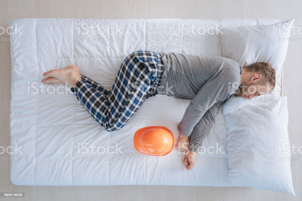 Serious professional engineer lying on the bed stock photo