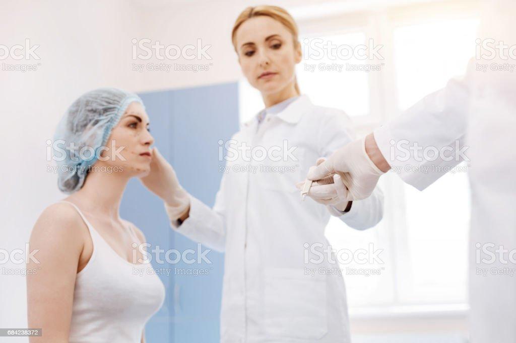 Serious professional surgeon taking a scalpel royalty-free stock photo