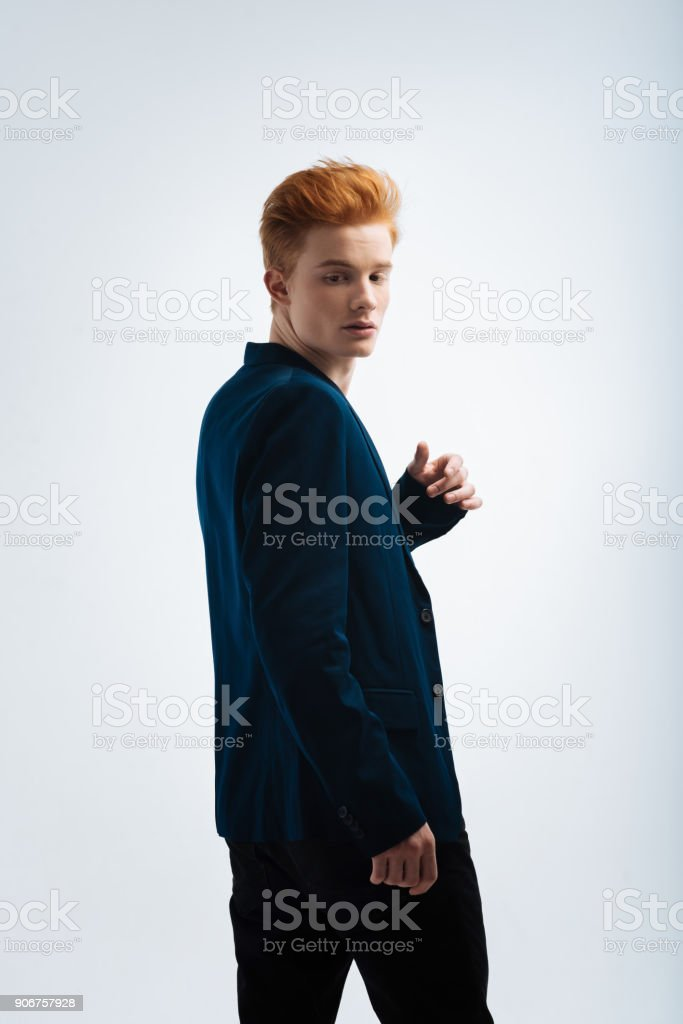 Serious red-headed man looking over his shoulder stock photo