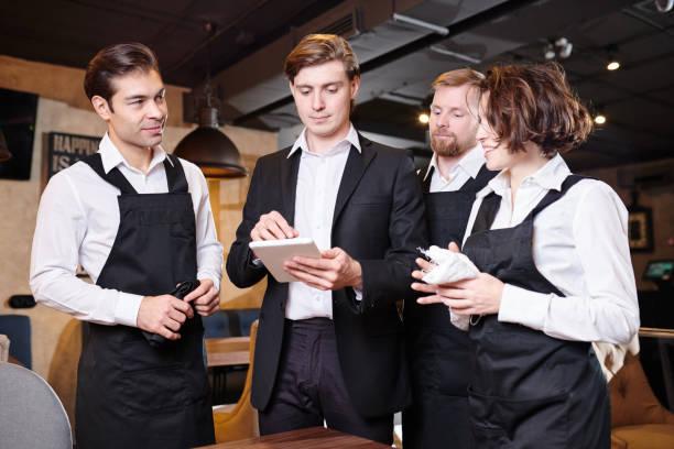 Ernsthafte Restaurantleiter Aufteilung der Verantwortlichkeiten unter den waite – Foto