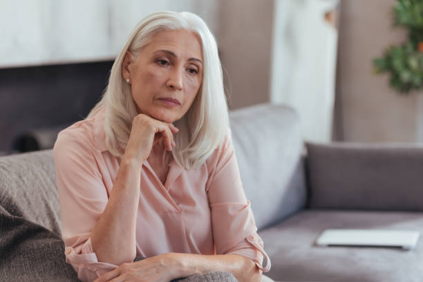 Serious sad aged woman thinking about her life stock photo