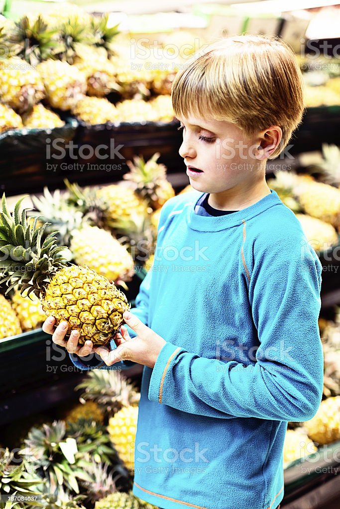 Serious schoolboy selecting perfect pineapple at market royalty-free stock photo