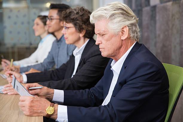 serious senior businessman reading document - lesen arbeitsblätter stock-fotos und bilder