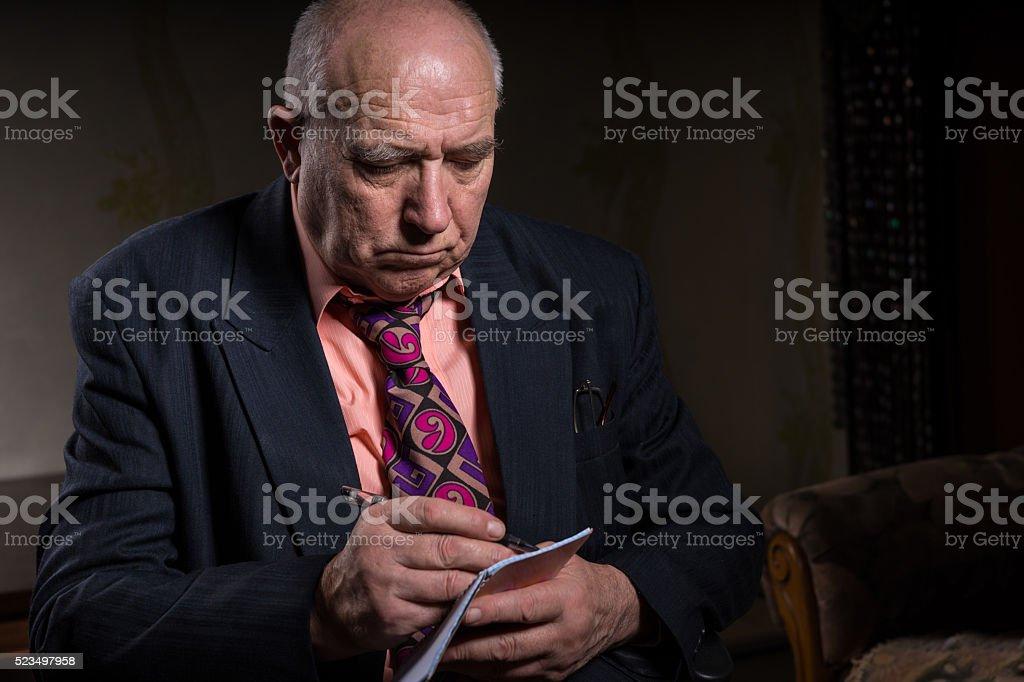 Serious Senior Businessman Taking Down Notes stock photo