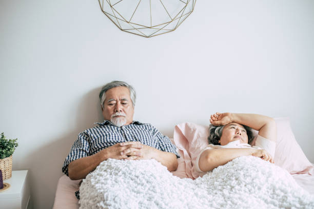 Serious senior couple looking away lying on bed Serious senior couple looking away lying on bed asian couple arguing stock pictures, royalty-free photos & images