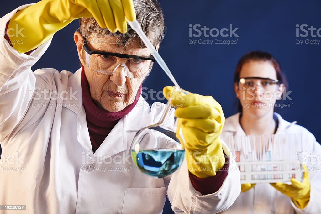 Serious senior female scientist in lab with young assistant stock photo