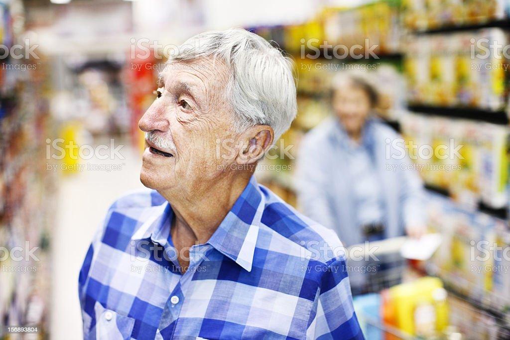 Serious senior man checks supermarket shelves seeking something stock photo