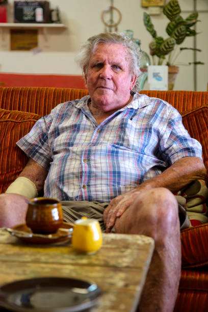 Serious senior man looking straight ahead while sitting on a couch in Queensland, Australia stock photo