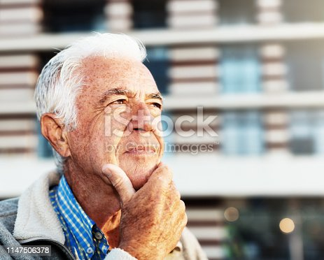 A good-looking senior man stands outside, chin on hand, looking up at the sky seriously.