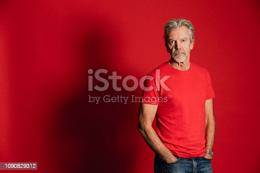 Portrait of a serious senior man standing in front of a red background.