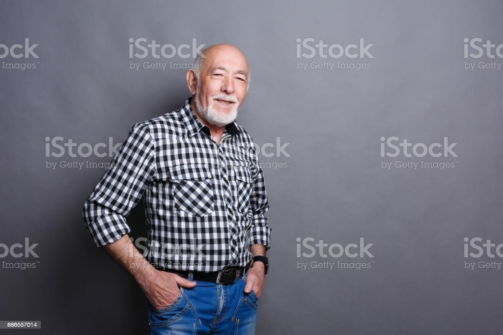 Serious senior man posing with hands on hips stock photo