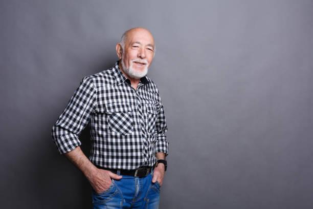 Hombre mayor serio posando con las manos en las caderas - foto de stock
