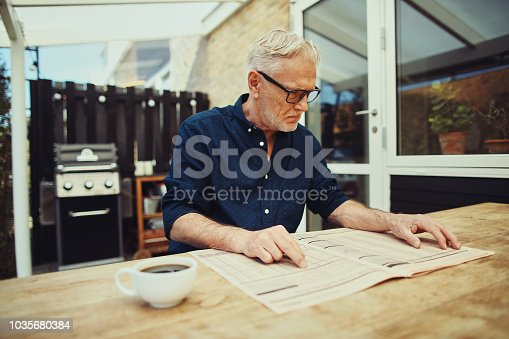 116379055 istock photo Serious senior man reading a financial newspaper on his patio 1035680384