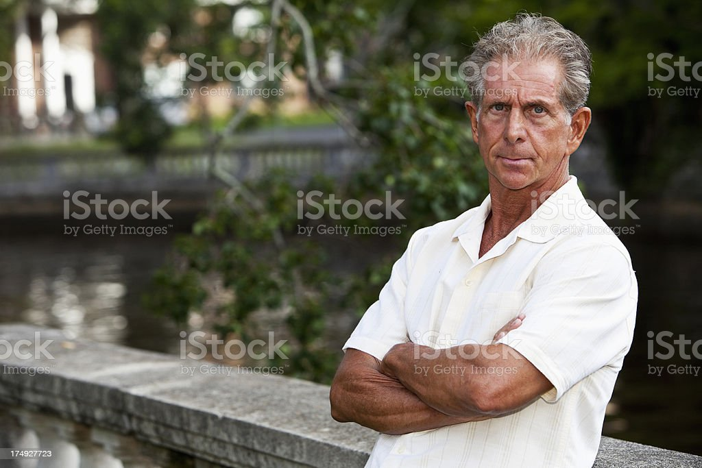 Serious senior man standing at waterfront stock photo