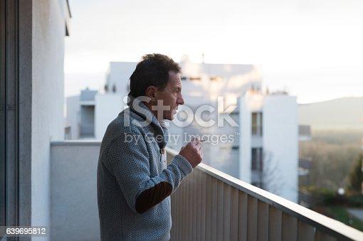 istock Serious senior man standing on balcony, smoking a cigarette 639695812
