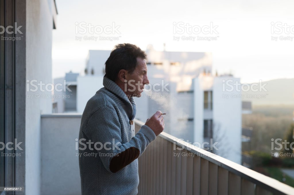 Serious senior man standing on balcony, smoking a cigarette stock photo