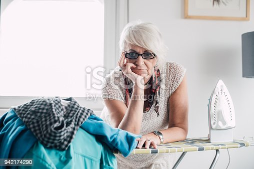 524159504 istock photo Serious senior woman ironing 942174290