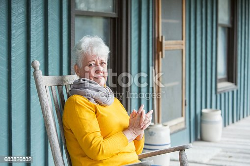 istock Serious senior woman sitting in rocking chair 683826532