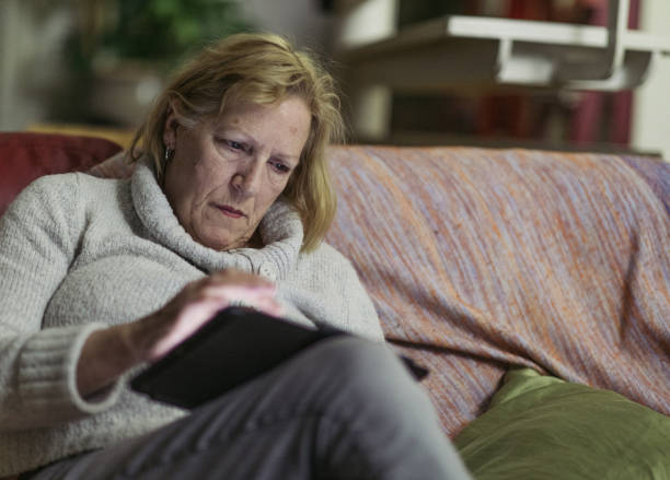 A serious senior woman, sitting on a couch, is reading important information on her tablet. stock photo