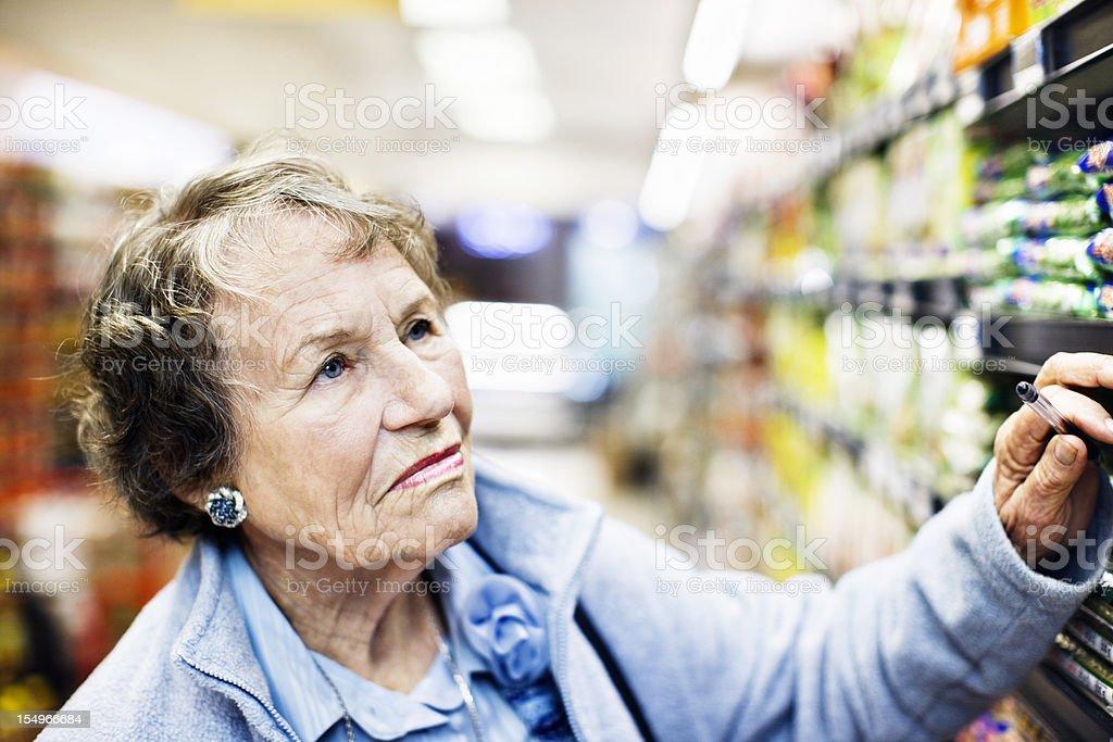 Serious senior woman supermarket shopper makes selection royalty-free stock photo