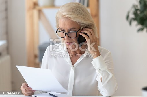 Concentrated senior businesswoman in glasses sit at office desk talk on cellphone reading paperwork document, focused middle-aged woman speak with client on smartphone discuss contract