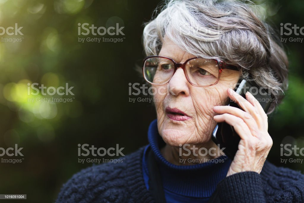 Serious senior woman  talking on phone outdoors seems concerned stock photo
